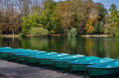 Small boats and trees in autumn Stock Image