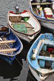 Small Boats on water. Boats with fishing nets, oars, tools moored together on the water Royalty Free Stock Images