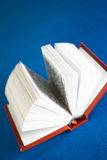Small book. Small red book opened on isolated blue background Stock Photos