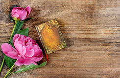 Small book and lush pink peonies on wooden table Stock Photos