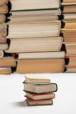 Small books with big books. A stack of small books with stacks of big books on the background Royalty Free Stock Photography