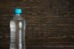 Small bottle of clean water with drops. On a dark wooden background, close-up with space for your text Stock Images