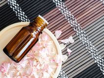 Small bottle with essential oil on the small plate with dry pink geranium flowers. Background with dried flowers petals. Aromatherapy, spa and herbal medicine royalty free stock photo