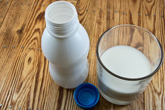 A small bottle of milk and glass of milk on wooden back Royalty Free Stock Photos