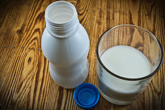 A small bottle of milk and poured a glass of milk on wood table Royalty Free Stock Images