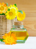 Small bottle of natural aroma oil and calendula flowers for spa, massage and aromatherapy Stock Photo