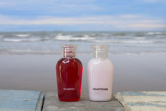 A small bottle of shampoo and conditioner with sea on the beach Royalty Free Stock Photo