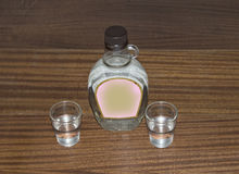 Small bottle of vodka and two glasses Stock Image
