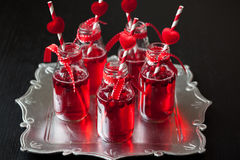 Small bottles with cranberry cocktail Royalty Free Stock Photos