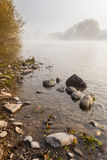 Small boulders on foggy shore in autumn. Foggy shore of the river in autumn with small boulders in the foreground Stock Image