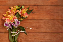 A small bouquet of Alstroemeria with a pearl thread on wooden brown background. A small bouquet of Alstroemeria with a pearl thread on a wooden background Royalty Free Stock Photo