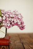 Small bouquet of lilac in glass vase as detail of interior, on wood background Royalty Free Stock Image