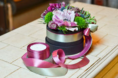 Small bouquet with pink flower in a box with ribbons. Bouquet with pink flower in a box with ribbons Stock Image