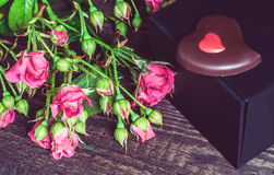 Small bouquet of roses and gift on a wooden background Stock Photography