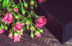 Small bouquet of roses and gift on a wooden background Royalty Free Stock Images
