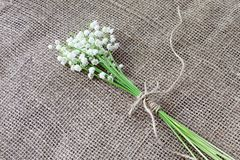 Small bouquet of white forest fragrant lilies of the valley tied with twine on coarse homespun jute fabric stock photography