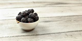 Small bowl with blackberries on wooden desk, space for text on right side.  stock images