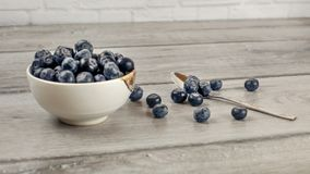 Small bowl of blueberries, some of them spilled next to spoon on. Gray wood desk Royalty Free Stock Images