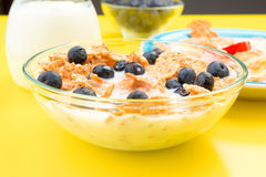 Small bowl of cereal and other berries on yellow Stock Photography
