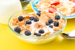 Small bowl of cereal and other berries on yellow Royalty Free Stock Photography