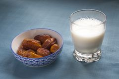 Muslim traditional basic iftar. A small bowl with dates and a glass of milk on a blue fabric background, ramadan and iftar concept. This food is also a Royalty Free Stock Photo