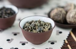 Small bowl of dry green tea leaves. Small ceramic bowl with dry green tea leaves on Japanese pattern tablecloth, close up royalty free stock images
