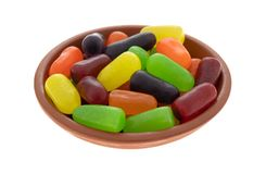 Chewy colorful candy in a bowl. A small bowl filled with chewy colorful sugar candy isolated on a white background royalty free stock photography