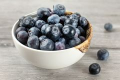 Small bowl full of blueberries, some of them spilled on gray woo. D desk Royalty Free Stock Photography