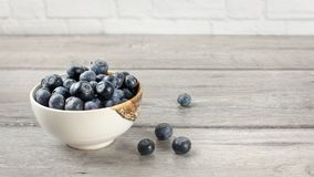 Small bowl full of blueberries, some of them spilled on gray woo. D desk stock photo