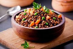 Small Bowl Of Lentils With Carrot And Peas. Close up of some organic brown lentils royalty free stock photo