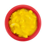 Small bowl of mac and cheese on a white background. Top view of a small red bowl filled with macaroni and cheese isolated on a white background Stock Photo