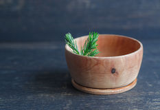 Small bowl made of juniper wood with juniper branch Stock Image