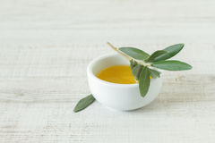 Small bowl with olive oil. Close-up of bowl with olive oil and olive branch kept on wooden table Stock Photo
