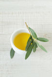 Small bowl with olive oil. Close-up of bowl with olive oil and olive branch kept on wooden table Stock Photography