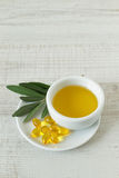 Small bowl with olive oil and natural pills. Close-up of bowl with olive oil, natural pills and olive branch kept on wooden table Stock Image