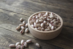 Small bowl of pistachios on wooden table Royalty Free Stock Photos