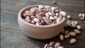 Small bowl of pistachios on wooden table stock footage