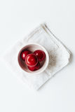 Small bowl of red plums on white vintage napkin Royalty Free Stock Image