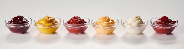 Small bowls of assorted sauces and dressings. Small bowls of assorted sauces, dips, marinades and dressings on white with reflections in a panorama banner stock photos