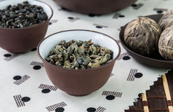 Small bowls of dry green tea leaves. Green tea leaves and small balls bundle of dried tea leaves on Japanese pattern tablecloth royalty free stock photos