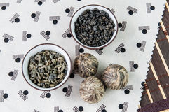 Small bowls of dry green tea leaves. And small balls bundle of dried tea leaves on Japanese pattern tablecloth royalty free stock images