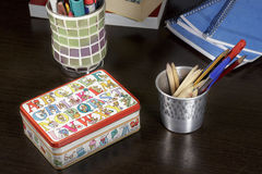 Small box with drawings of toy bears on a desk. A small metal box decorated with drawings of teddy bears with diverse objects or representing different Stock Photos