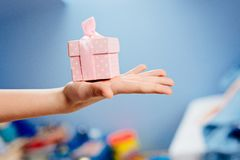 Small box - a gift for mother - Mother`s Day. Close up on little boy`s hands holding small box - a gift for his mother - Mother`s Day Stock Image