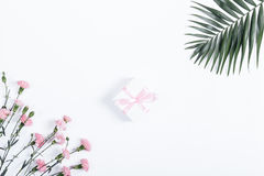 Small box with pink ribbon and flowers lie on a white table Stock Image