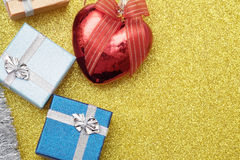 Small boxes for gift and christmas heart shaped red ball on yellow Stock Photos