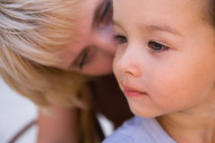 Small boy. Mam to whisper in son's ear. Focus on child Stock Images