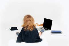 Small boy in academic gown. Small boy child in black gown with long curly blond hair sitting back near academic squared cap open notebook diaries and wooden Royalty Free Stock Photos