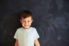 Small boy against blackboard smiling sincerely Royalty Free Stock Images