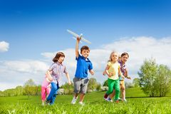 Small boy with airplane toy and friends running Stock Photo