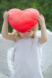 Small boy in angel wings and heart pillow Royalty Free Stock Photography